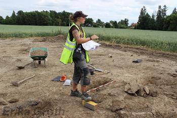 Guiden visar var stolphålen finns. Stolparna bar upp taket i ett bostadshus under romersk järnålder.
